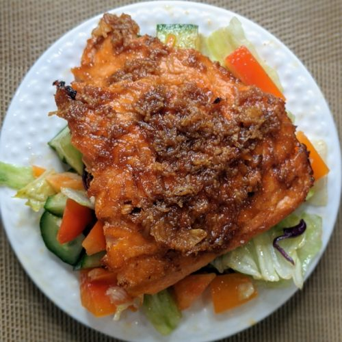Glazed Ginger Salmon atop of tossed salad on white plate