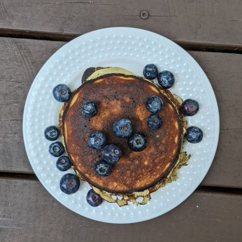 Stack of pancakes surrounded by blueberries on a white plate